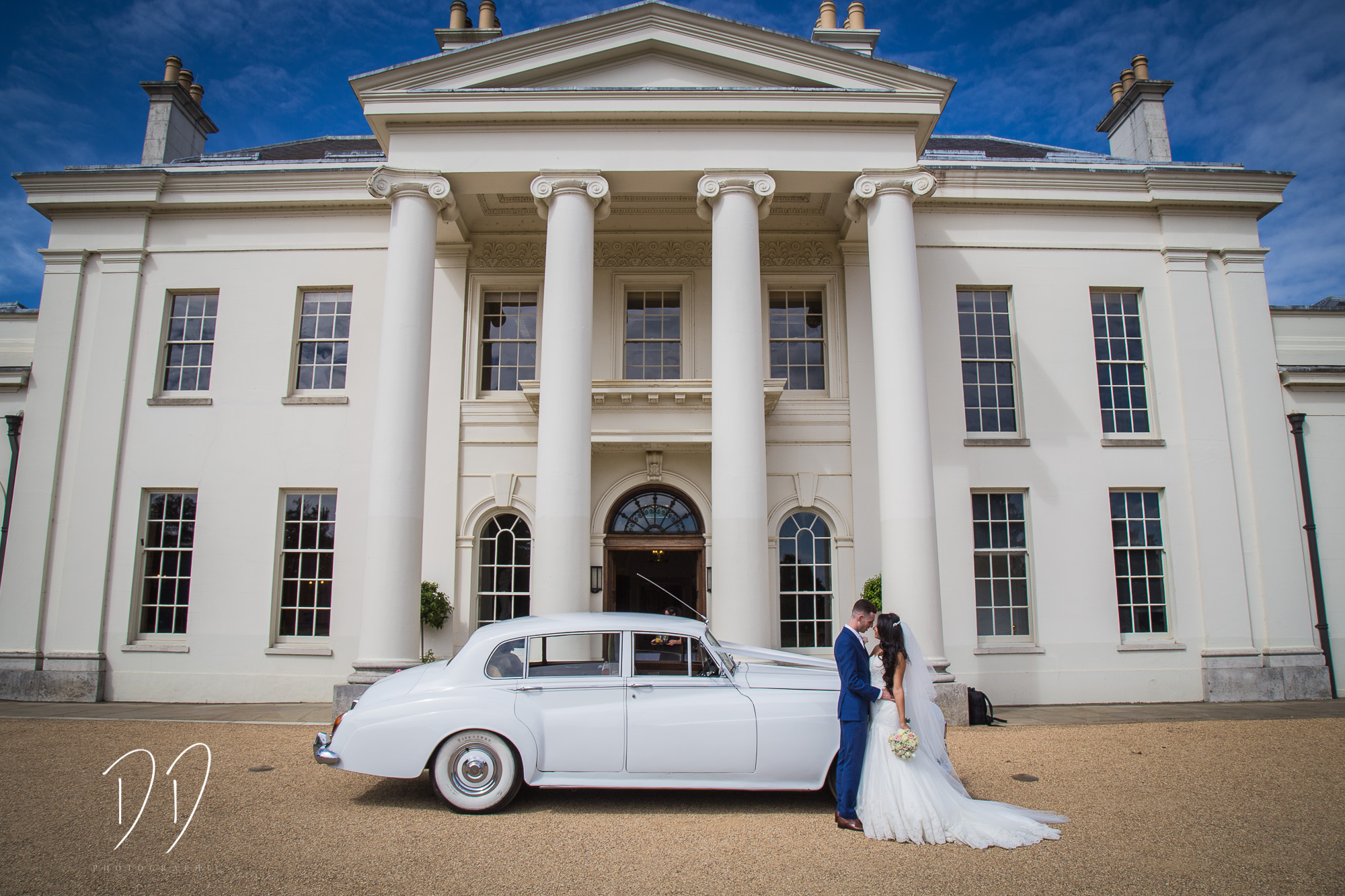 Image outside the front of Hylands House wedding venue in Chelmsford. Couple in front of white wedding car.
